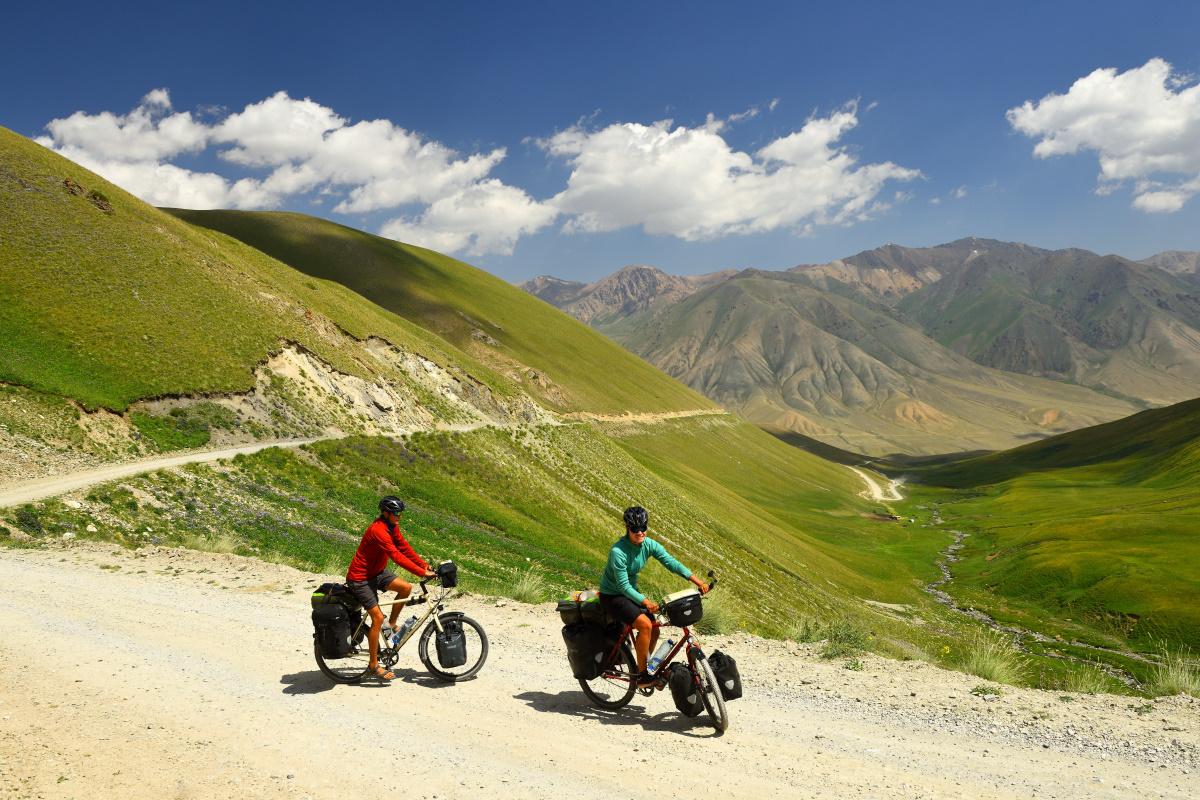 Zwei Radfahrer mit bepakten Reiserädern auf einer Schotterstraße in den Anden.